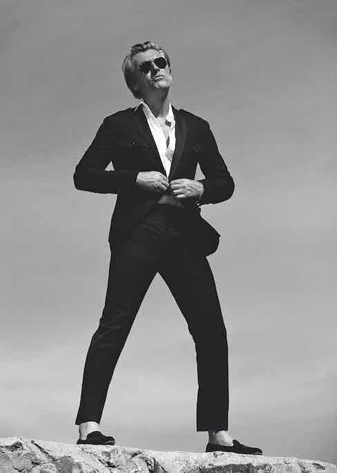 Black linen safari jacket with silk lapels, white cotton shirt and black wool tuxedo trousers, all Ralph Lauren Purple Label; black velvet, embroidered slippers, Edward Green; yellow gold aviators with green lenses, Ray-Ban; pink silk paisley print pocket handkerchief, Serà Fine Silk at The Rake.