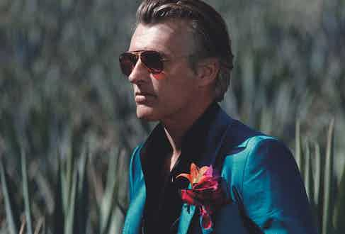 Turquoise silk jacket, Dolce & Gabbana; black silk shirt, Cifonelli; blue and red silk pocket handkerchief, Serà Fine Silkat The Rake; copper aviator sunglasses with crystal red lenses, Ray-Ban; coral, onyx and yellow gold bracelet, navy silk and silver pendant bracelet, Rubinacciat The Rake