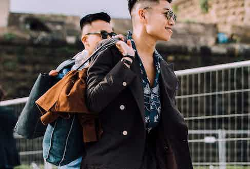 A chocolate brown double-breasted Seersucker suit worn with a camp-collar shirt and denim tote bag.