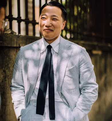 Homie Yang in the classic white/blue Seersucker, paired with a white button-down shirt (worn unbuttoned) and a black knitted tie.