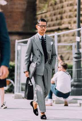Tomoyoshi Takada perfectly demonstrating how to boss a double-breasted grey suit with a cropped turn-up trouser. Note the addition of velvet slippers to rip up the rule book.