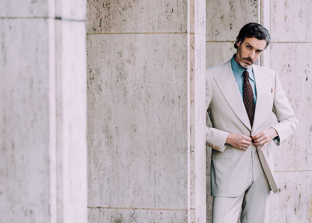 A neutral tone suit such as this one by Edward Sexton can be the perfect antidote to the charcoal grey work suit, especially when you add refreshing elements such as a blue denim or linen shirt and a contrast burgundy tie.