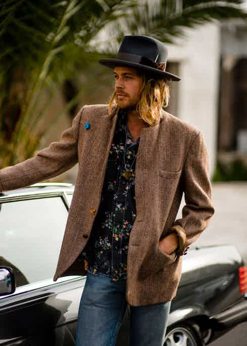 Nick pairs the bash fedora with a tailored jacket and jeans for a laidback look.