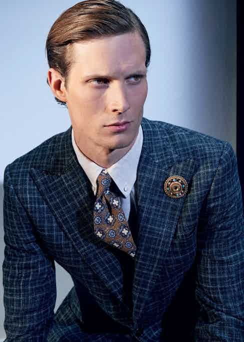 Charcoal grey check wool jacket, Cifonelli; cream linen button-down shirt, Turnbull & Asser; mid-blue cotton and wool trousers, Anderson & Sheppard Haberdashery at The Rake; brown and blue silk print tie, Franceso Marino for The Rake.