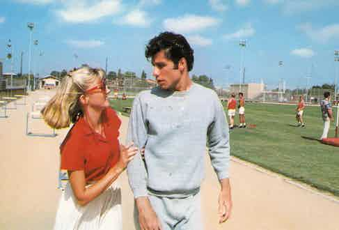 John Travolta in Grease wearing the classic two-piece athletic suit.