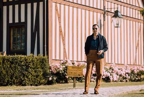 English heritage in the Normandy countryside: Alexander wears Edward Sexton tobacco brown Hollywood trousers with an Anderson & Sheppard shawl collar cardigan.