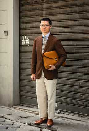 Zing Chen uses the application of a geometric printed tie to bring together his brown jacket and cream trousers.