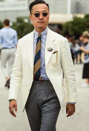 Kenji Cheung of Bryceland's & Co balances his cream single-breasted jacket with a tailored grey wool trouser.