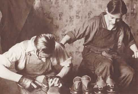 A young Norman Walsh hand welting a pair of leather sports shoes.