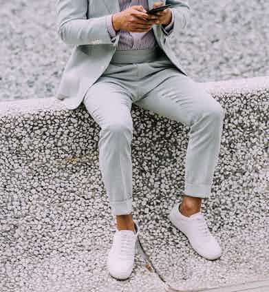 A pastel blue suit and striped shirt paired with minimalist white sneakers. A crisp white pocket square co-ordinates perfectly with the white trainers.