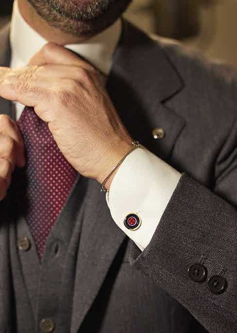 Cristiano models a blue and red cufflink with a bespoke three-piece suit.