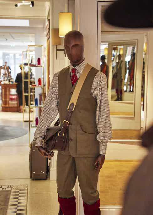 A mannequin stylishly attired in smart countryside garb and sporting a cartridge bag for a shoot.