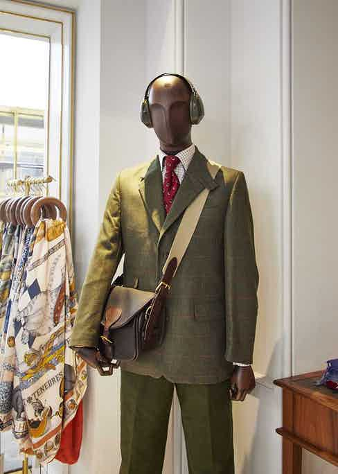 A mannequin wearing tweed blazer with tie and shirt combo and ear muffs for protecting against the cold.