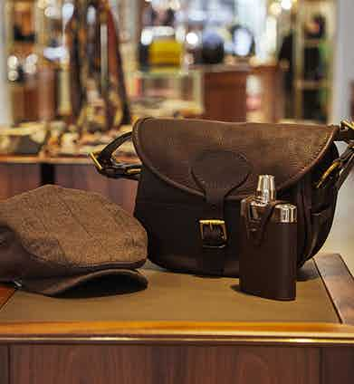A peaked cap, a cartridge bag, and a hip flask - everything a gentleman needs for a successful shoot.