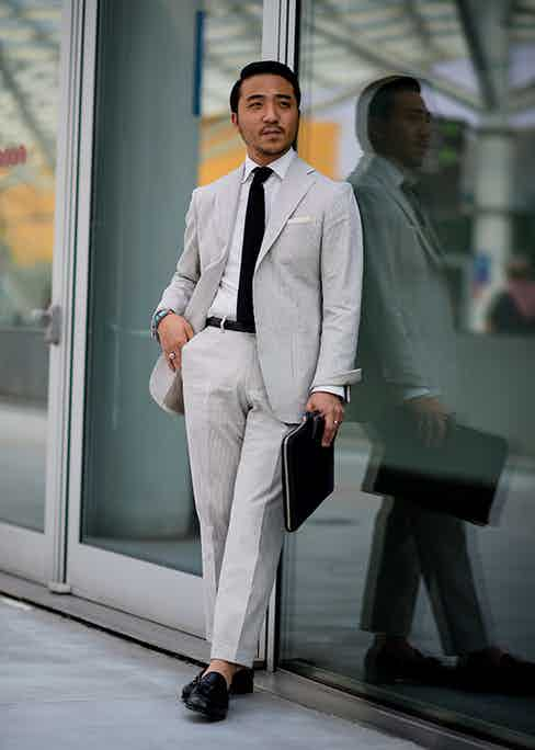 A monochrome palette eschews uniformity by simply adding a good-sized turn-up to the trousers, creating something of an insouciant edge to an otherwise business-like suit.
