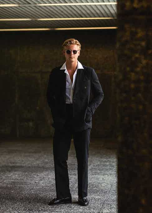 Relaxed, wide-cut tailoring in darker hues will allow a crisp white cuban collar to stand out.