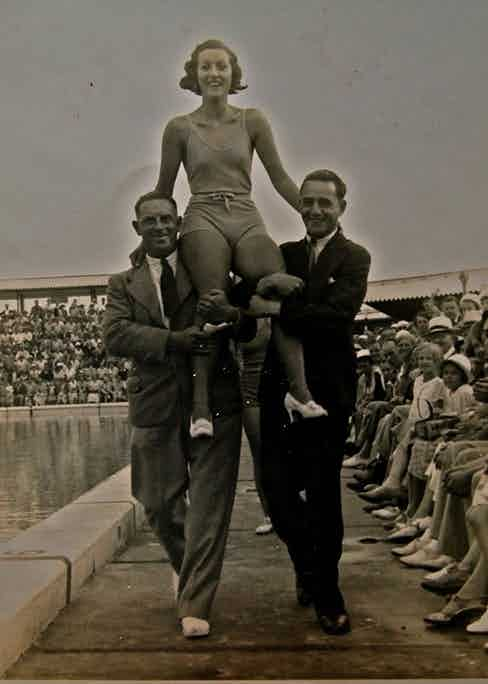 Stacey Wood's grandmother Joan pictured here hitching a ride on the shoulders of two suited gentlemen.