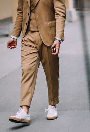 A camel brown three-piece suit styled with crisp white rubbed-soled sneakers. The simple touch of turning up the trouser leg injects excitement into the look.