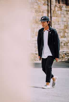 Two-tone Vans paired with oversized white T-shirt and black trousers and jacket, the monochrome palette is offset by an orange bandana.