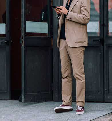 Burgundy Vans add a point of contrast to relaxed sand grey suiting.