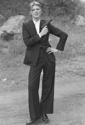 Bowie accessorises his oversized suiting with a gun for an accent of devil-may-care insouciance. Photograph by Alamy.