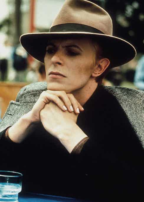 David Bowie in brown Fedora with grey herringbone coat draped rakishly over his shoulders. Photograph by Alamy.