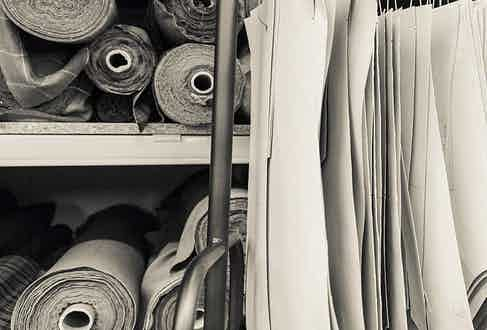 Rolls of fine fabrics stored in William & Son's workshops. Image courtesy of William & Son.
