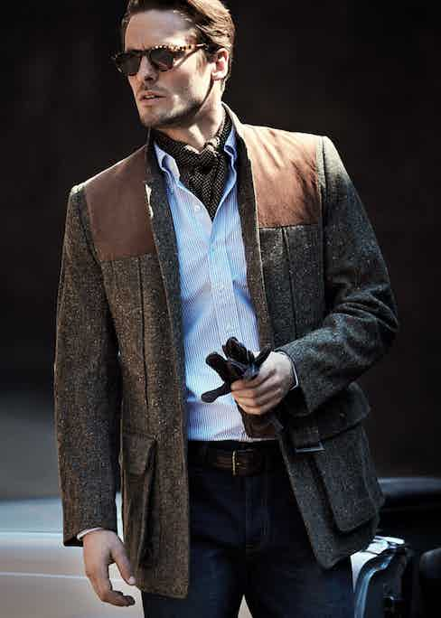 Olive Donegal wool tweed Norfolk jacket, Lucan for The Rake; blue cotton stripe shirt, Drake's; indigo denim jean, Wrangler; brown leather woven belt, R.M. Williams; brown leather gloves, Brunello Cucinelli. Photograph by Neil Gavin, styling by Veronica Perez.