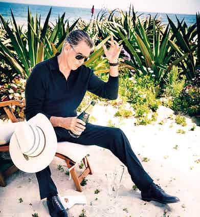 Black knitted cotton long-sleeved polo shirt, Tom Ford at Mr Porter; black wool trousers, Brioni; black cotton socks, Pantherella at The Rake; black leather lace-up derby shoes, George Cleverley. Straw hat, watch and sunglasses, property of Pierce Brosnan.