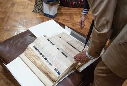 Here, Mariano Rubinacci rifles through his family's ledger book that has cloth samples dating back to the 1930s. It was in this ledger that we found the houndstooth cloth to this suit.