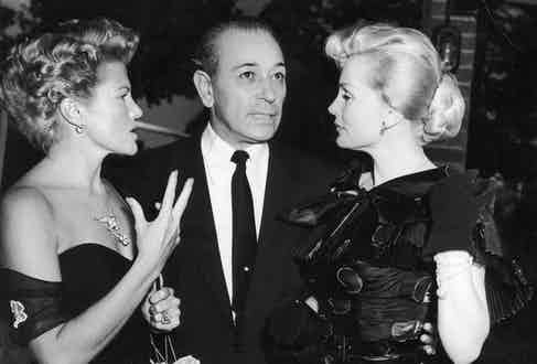 Chatting with  actresses Zoe Gail and Zsa Zsa Gabor at a farewell party he hosted before leaving England for Italy and the U.S., 1952. Photograph by Getty Images.