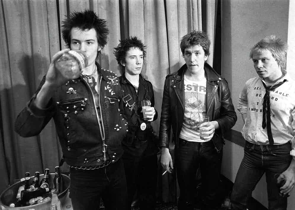 Celebrating with Johnny Rotten, Steve Jones and Paul Cook after signing a record deal, 1977. Photograph by Rex Features.