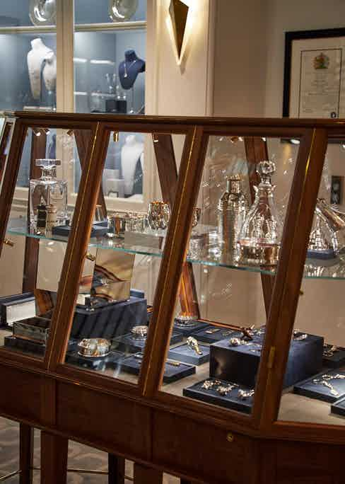 A display case of crystal glass bar wear and exquisite silver at the Bruton Street headquarters.