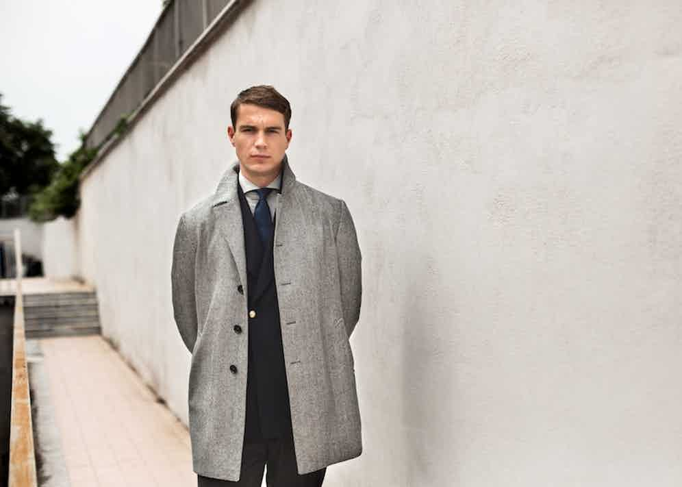 Grey wool herringbone overcoat with a double-breasted navy blazer from De Petrillo. Photography by Shaun Darwood.