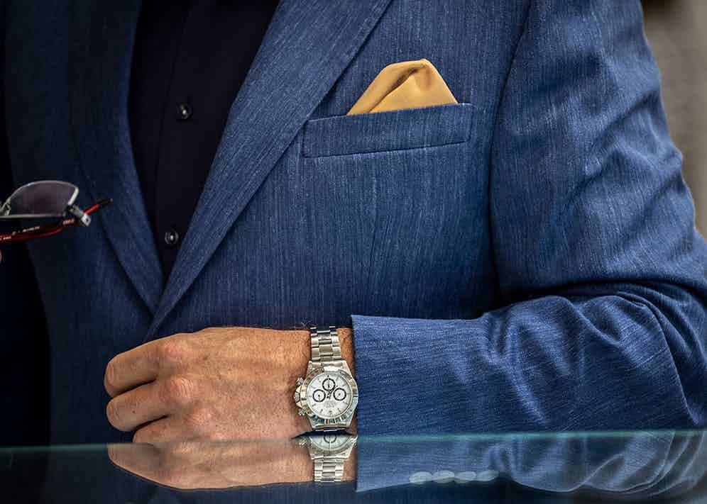 A Rolex Daytona beautifully offset by a striking combination of blue suit and contrast yellow pocket square.