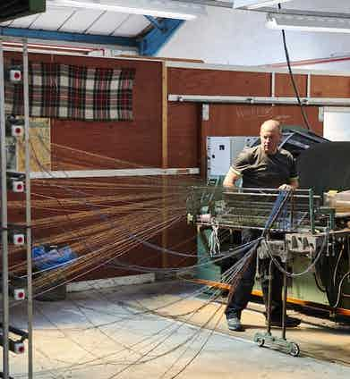 A craftsperson weaves the warp. Photo by James Holborow.