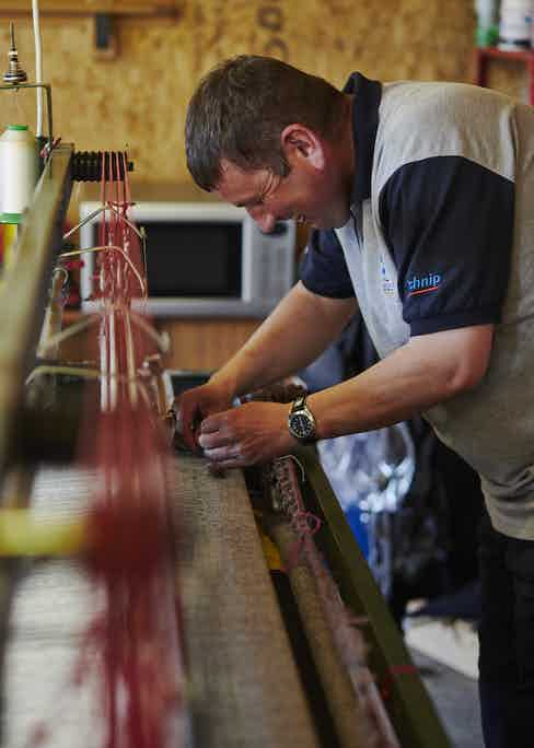 Calum George Buchanan, an independent weaver, applies the weft to the warp. Photo by James Holborow.