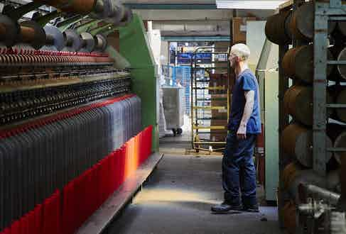 A craftsperson at the Shawbost mill inspects the spinning process. Photo by James Holborow.