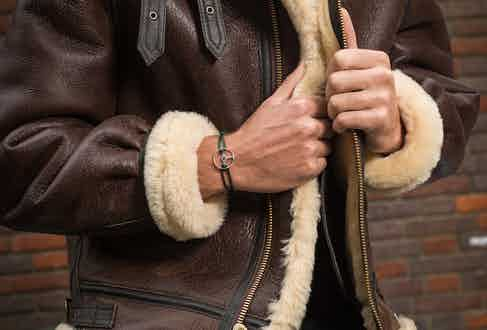 Brown B3 Shearling jacket, Schott; Black cotton short sleeve classic crew neck T-shirt, Sunspel; Black raw Japanese selvedge jean, The Workers Club; 24H Le Mans edition bracelet on black cord, The Mechanist; Brown wool and silk houndstooth neckerchief, Anderson & Sheppard.