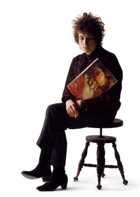 Dylan is pictured smoking a cigarette and holding a prop in Schatzberg's photography studio in the mid-1960s. © Jerry Schatzberg. Courtesy of ACC Art Books.