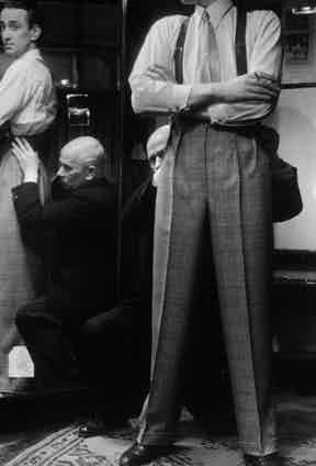 A Savile Row tailor fits a customer with a pair of trousers, circa 1939. Photograph by Getty Images.