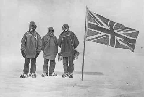 Circa 1909: Irish explorer Sir Ernest Henry Shackleton and two members of his expedition team beside a Union Jack within 111 miles of the South Pole, a record feat. (Photo by Hulton Archive/Getty Images)