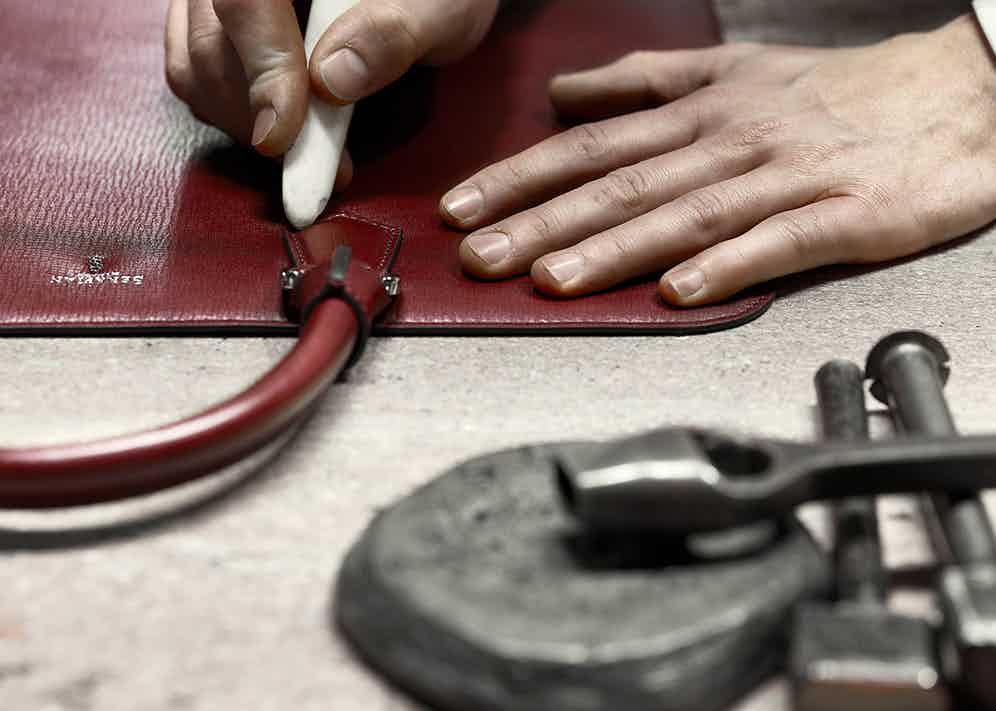 A Serapian craftsman carefully applies the finishing touches to a bag.