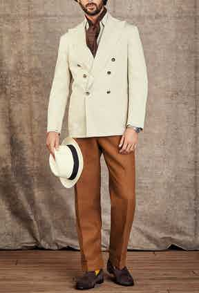 Caribbean: Jacket by Rubinacci; Shirt by Edward Sexton; Neck tie by Fumagalli 1891; Trousers by Edward Sexton; Socks by The London Sock Company; Loafers by Baudoin & Lange; Sunglasses by Oliver Goldsmith; Hat by Lock & Co; Watch is a very rare Rolex 1965 GMT-Master with tropical gilt glossy dial in stainless steel.
