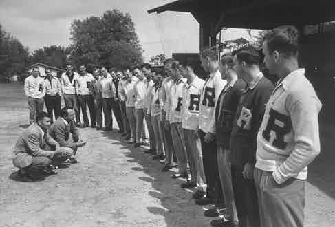 Football players line up in front of their coach. Photograph by Getty Images.