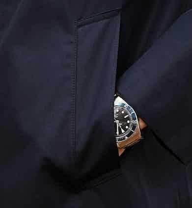 The coat features front slash pockets.