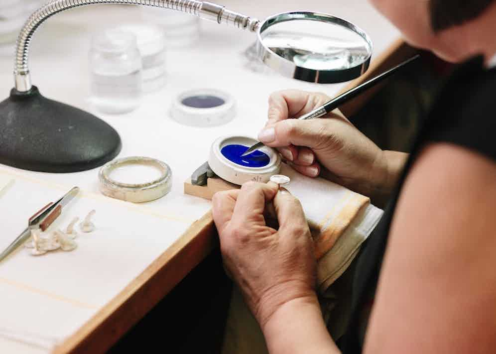 A craftswoman applies a blue enamel via a pen of sorts.