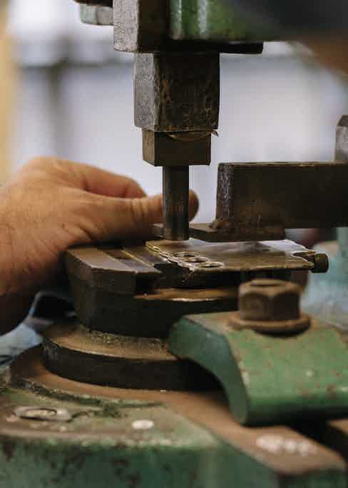 An oval shaped cufflink is pressed using ancient machinery.