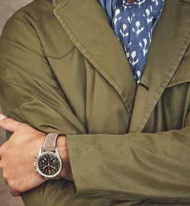 Jacket by Grenfell; Shirt by Emma Willis; Scarf by Anderson & Sheppard; Trousers by Rubinacci; Boots by Ludwig Reiter; Hat by Lock & Co; Watch is a circa 1955 Breitling Navitimer 'Pre-806' in stainless steel.