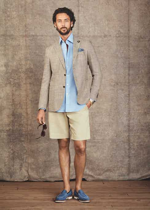 Jacket by Lardini; Shirt by Emma Willis; Pocket Square by Rubinacci; Shorts by Anderson & Sheppard; Loafers by George Cleverly; Sunglasses by Oliver Goldsmith, Watch is a very rare Rolex Daytona with diamond and rainbow-coloured multi-gem set in yellow gold.